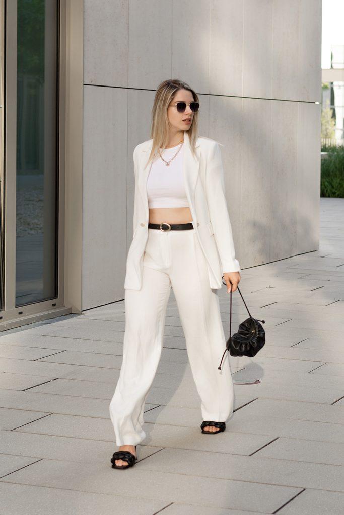 Saskia Denise in einem Weißen Blazer, einem Crop Top und einer weißen Hose mit weitem Bein - Bild zum Beitrag Outfits für wechselhafte Sommertage