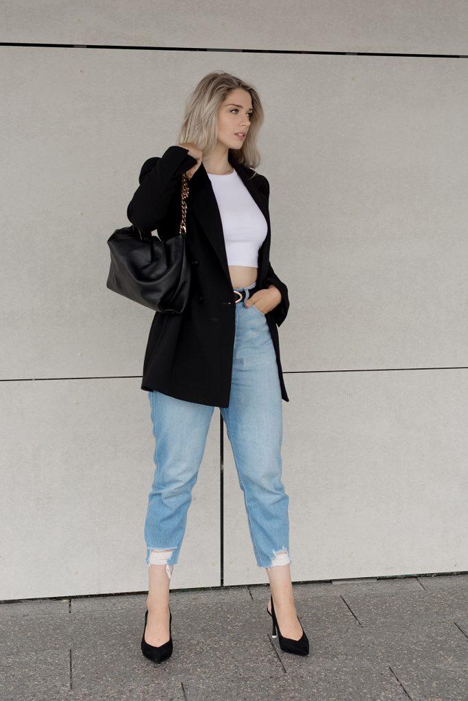 Saskia Denise in einem schwaren klassischen Longblazer einem Crop Top und einer Mom-Jeans - Bild zum Beitrag Outfits für wechselhafte Sommertage
