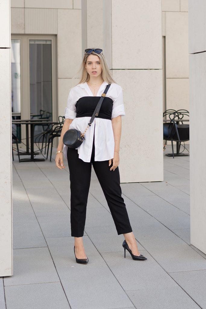 Saskia Denise in einem weißen Oversized Hemd und schwarzer eleganter Hose - Bild zum Beitrag Outfits für wechselhafte Sommertage